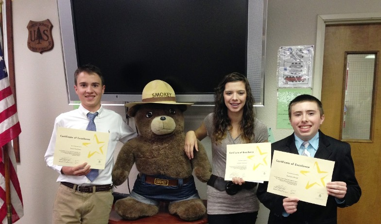 Three high school students holding up paper awards.