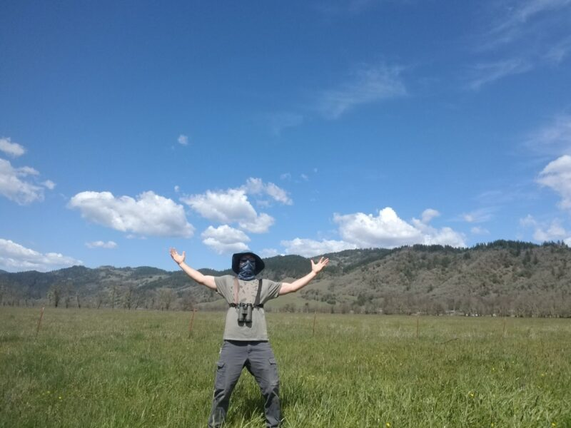 Man social distancing in field with face mask