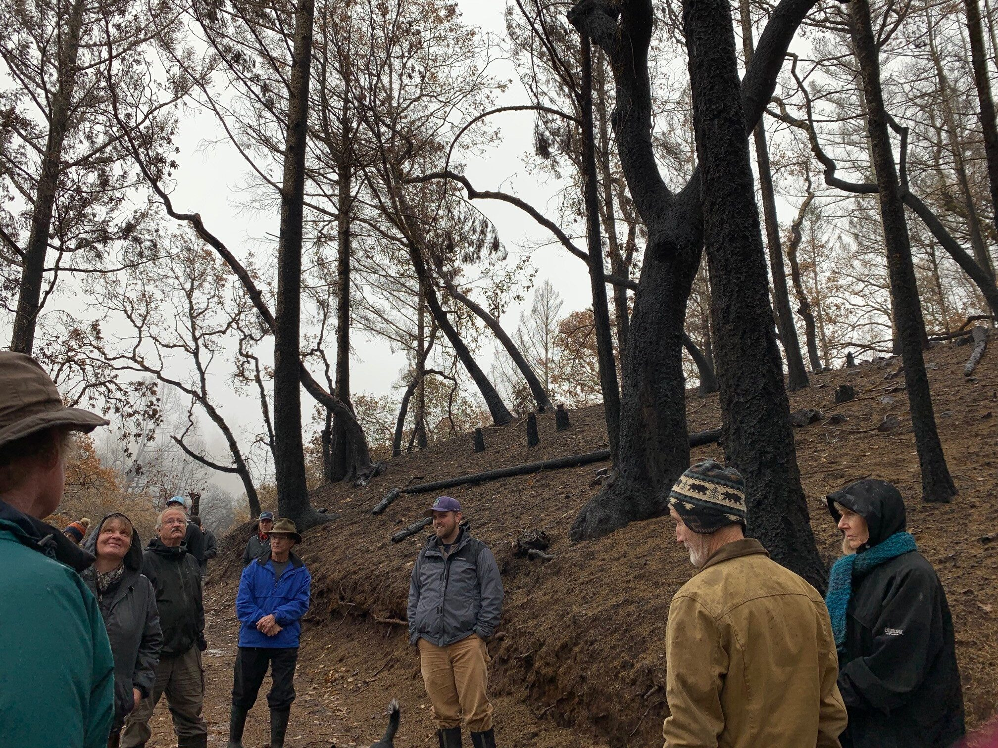 Staff speaks to small group near burned trees
