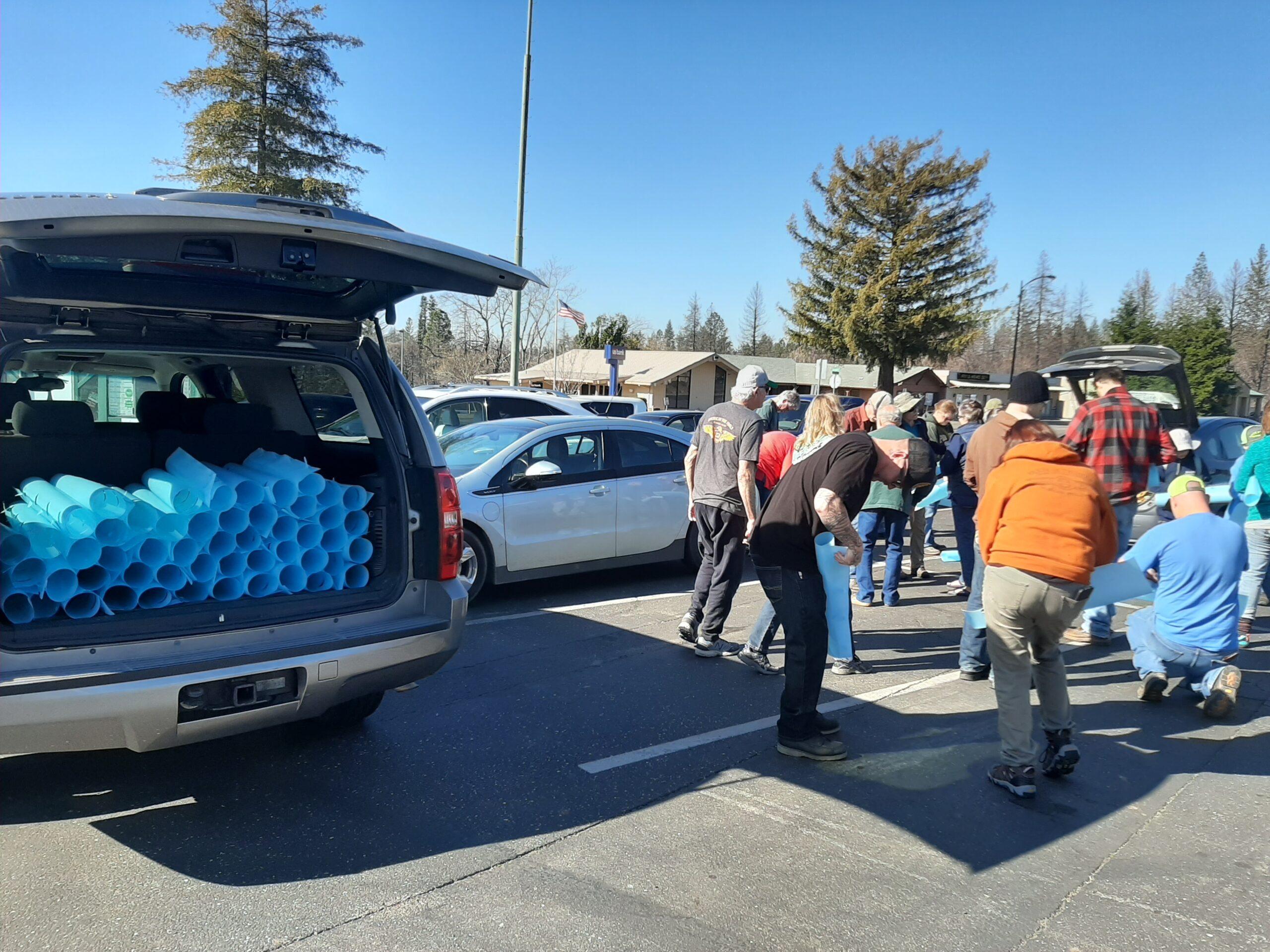 Volunteers in parking lot standing next to pile of tree protectors